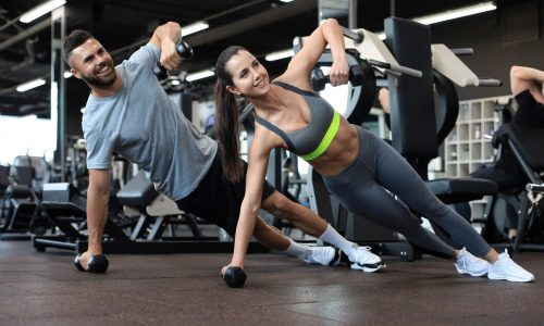 Strong man and woman holding dumbbells in plank position at the gym